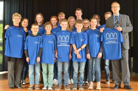 Der Vorsitzende des Förderkreises Nils Kambach (r.) überreicht die Shirts an die Schulleiterin Frau Woltmann (l.) und laufbegeisterte Schülerinnen und Schüler.